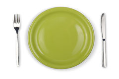 Knife, green plate and fork isolated top view Royalty Free Stock Photo