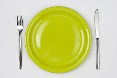 Knife, green plate and fork top view Royalty Free Stock Photography