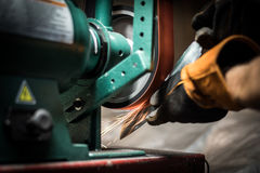 Knife grinding. Close up of worker using a grinder to sharpen a knife royalty free stock photos