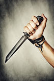 Knife in hand. Male hand holding combat black Knife royalty free stock images