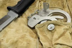 Knife and Handcuffs on the Camouflage Background Stock Photos