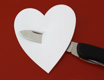 Knife and heart. Knife and white heat on dark red background royalty free stock photos