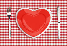 Knife, heart plate and fork on red tablecloth Royalty Free Stock Photos
