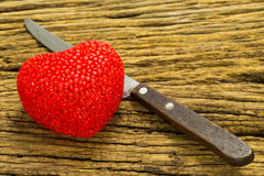 Knife and heart on wooden background.  royalty free stock image