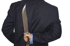 Knife hidden behind the businessman Royalty Free Stock Photo