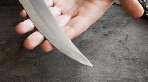 Knife with its blade in hand Stock Images