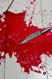 Knife and lot of blood splash on tile floor Stock Images