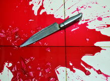 Knife and lot of blood on tile floor Royalty Free Stock Photos