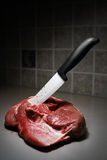 Knife in meat. Kitchen ceramic knife in the meat on the kitchen stock photo
