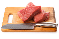 Knife and meat on the wooden board Royalty Free Stock Image