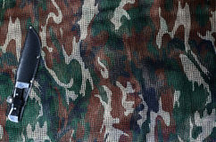 Knife on military camouflage net background Stock Photography