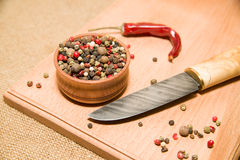 The knife, a mixture of grains of pepper on a wooden surface Stock Image