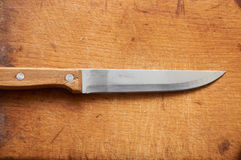Knife on an old chopping board Royalty Free Stock Images