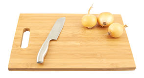 Knife and onions over a cutting board isolated Royalty Free Stock Images