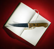 Knife on opened book Royalty Free Stock Photography