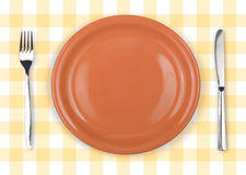 Knife, orange plate and fork on checked top view Stock Image