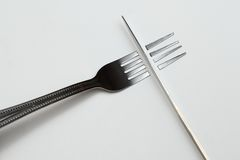 Knife Over Fork. This is a creative shot of a knife cutting a fork Stock Photo