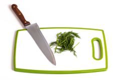 Knife and parsley lying on a cutting board. Close-up view Stock Photo