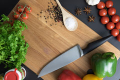 Knife parsley tomatoes salt spice and red green yellow peppers. Knife, parsley, tomatoes, spice, salt and peppers on clean wood backgorund Royalty Free Stock Photography