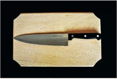 Knife on a piece of wood. NA steel knife on a shredder Stock Photo