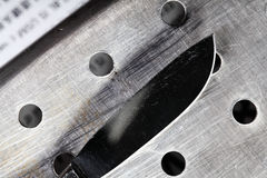 Knife on the pierced metal surface Royalty Free Stock Photo