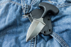 Knife with plastic case. Close up. Knife with plastic case. Background jeans. Tactical royalty free stock image