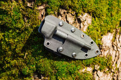 Knife with the plastic kydex sheath in the forest background. Plastic kydex sheath in the forest background. survival and bushcraft concept stock photo