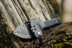 Knife with the plastic kydex sheath in the forest background. Survival and bushcraft concept stock photo