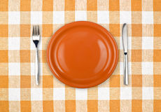 Knife, plate, fork on checked tablecloth Stock Photography