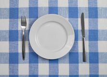 Knife, plate and fork checked tablecloth top view Stock Photo