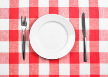 Knife, plate and fork checked tablecloth top view. Knife, white plate and fork on red checked tablecloth Royalty Free Stock Photos