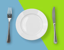 Knife, plate and fork on color backdrop top view Royalty Free Stock Photography