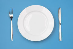 Knife, plate, fork on colorful background top view Royalty Free Stock Photography