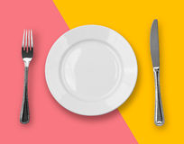 Knife, plate and fork on colorful top view Royalty Free Stock Images