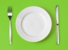 Knife, plate and fork on green top view Stock Photography