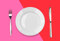 Knife, plate and fork on red colorful top view Royalty Free Stock Photography