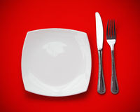 Knife, plate and fork top view. Knife, square white plate and fork on red background royalty free stock photo