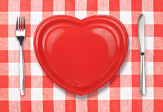 Knife, plate in heart shape and fork on tablecloth. Knife, red plate and fork on checked gingham tablecloth Royalty Free Stock Photos
