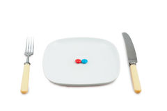 Knife, plug and plate with red and blue tablets. On white background Stock Photo
