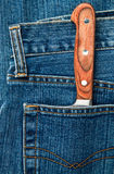 Knife in a pocket. Blue jeans pocket with kitchen knife Royalty Free Stock Image