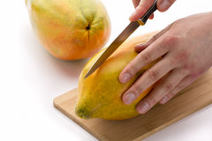 Knife Positioned For A First Cut Through A Papaya Royalty Free Stock Image