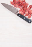 Knife and raw meat at the wooden board with copy space Stock Photography