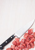 Knife and raw meat at the wooden board with copy space. Food background of knife and raw meat at the wooden board with copy space Royalty Free Stock Photo