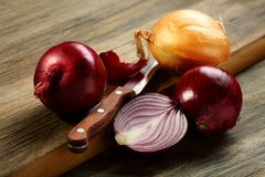 Knife,red onion and a half. Royalty Free Stock Photo