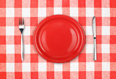 Knife, red plate and fork on checked tablecloth Royalty Free Stock Images