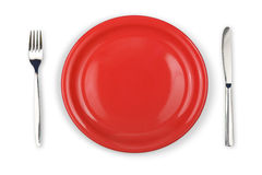 Knife, red plate and fork isolated Royalty Free Stock Photo