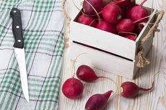 Knife and red radishes in a wooden box. Knife and red radishes in a wooden box on wooden desk Stock Images