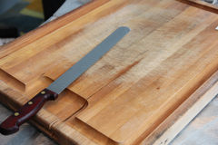 Knife resting on wooden cutting board Royalty Free Stock Photos