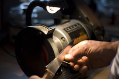 KNIFE SHARPENING. A large kitchen knife is being sharpened royalty free stock photos