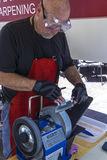 Knife sharpening. Man wearing safety goggles sharpens knife on machine at outdoor market Royalty Free Stock Photos
